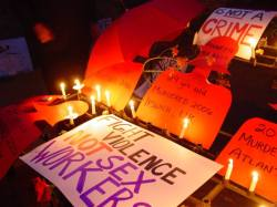"Candles and messages commemorating dead sex workers: ""Annette Nicholls, 29 years old, Murdered 2006, Ipswich, UK,"" ""Fight violence, not sex workers."""