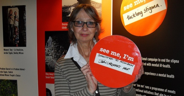 "Jean Urquhart MSP supporting See Me. Jean is holding a round board with the words ""see me, I'm committed to inclusion""."