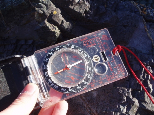 A geology student uses a compass-clinometer on a geology field trip.