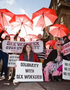 Women from the Sex Workers' Open University demostrate with red umbrellas and placards reading 'Solidarity with sex workers'.